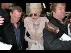 The alleged gloved groper is held back by security as Lady Gaga leaves her Paris hotel on December 20
